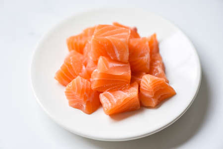 Raw salmon filet cube on white plate and white table background.