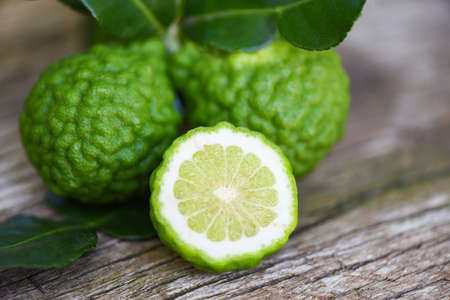 Fresh bergamot fruit, Kaffir Lime, Citrus bergamia with leaf on wooden table / Slice bergamot citrus fruit essential oil concept Banco de Imagens