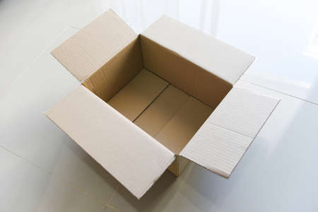 Open cardboard box on floor background, High angle view of an empty cardboard box or Parcel box Banco de Imagens