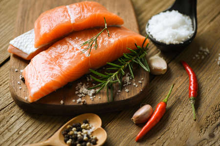 Raw salmon filet with herbs and spices on wooden background.