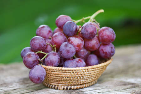 Ripe red grape in basket on wooden and natute green background , Fresh grape fruit