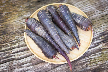 purple carrot on wooden plate , fresh carrot for cooking vegetarian on the table