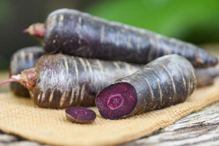 purple carrot on the sack, fresh carrot for cooking vegetarian on wooden table