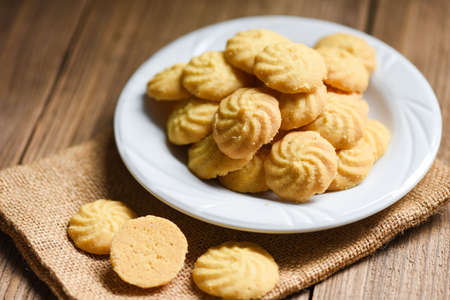 breakfast cookies vanilla on white plate and wooden background, mini cookies biscuits