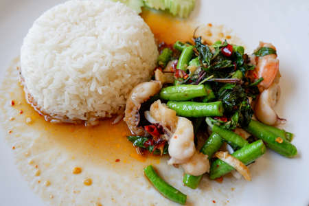 Yard long bean stir fried seafood squid shrimp prawn with holy basil and rice, Thai food spicy fried recipe with cucumber and chili