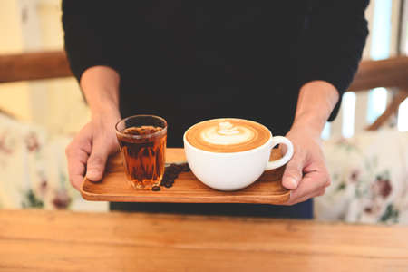 Coffee cup in hand on wooden table in cafe with coffee beans background, Served Coffee Cappuccino or latte and Tea
