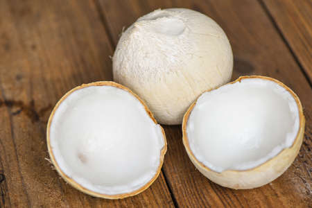 cut half coconut and fresh coconuts for food on wooden table