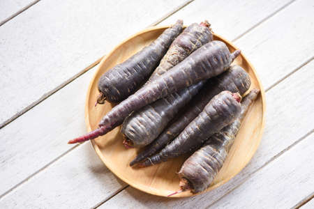 purple carrot on wooden plate , fresh carrot for cooking vegetarian on wooden table