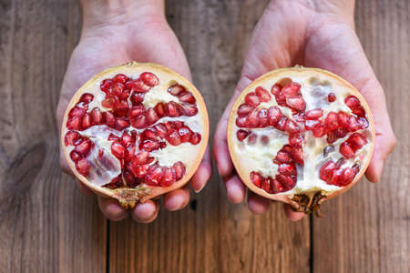 Pomegranate fruit cut half on hand, ripe pomegranate with seeds on wooden table background