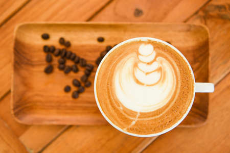 Coffee cup on wooden table in cafe with coffee beans background, Cappuccino or latte coffee, top view 写真素材