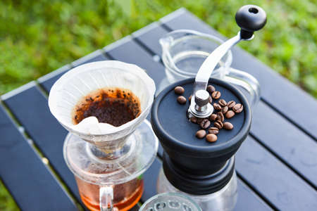 drip coffee barista pouring water on filtered brewing, make cup hand drip coffee in glass jar on outdoors 写真素材