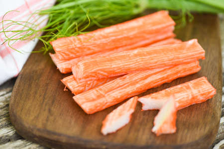 Crab sticks on wooden cutting board and vegetable , Fresh crab sticks surimi ready to eat japanese food