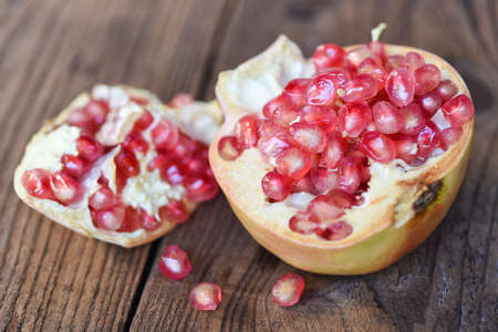 Pomegranate fruit and cut half ripe pomegranate with seeds on wooden table background