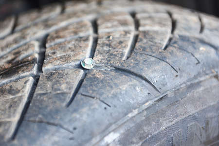 Car tires nail embedded in the broken tire, Screw in the black tire. Damaged tire problems and solutions concept.