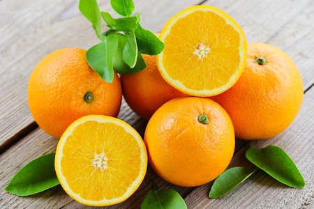 Orange fruits with leaf on wooden background, fresh orange slice and leaves healthy fruits Imagens