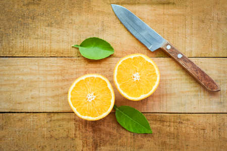 Fresh orange slice and leaves healthy fruits, Orange fruits with leaf kitchen knife on wooden background - top view