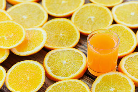 Fresh orange juice in the glass with orange fruit on wooden background, healthy fruits and orange slice
