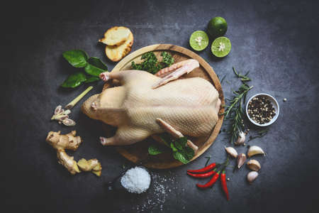 Raw duck with herb spices ready to cook on dark palte, Fresh duck meat on wooden tray for food, Raw whole duck - top view