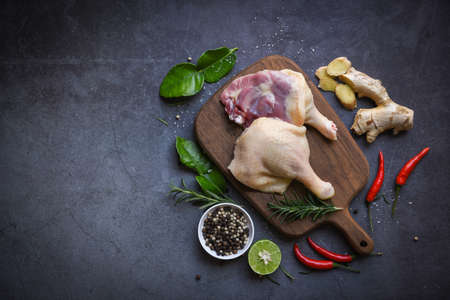 Raw duck legs with herb spices ready to cook on wooden cutting board, Fresh duck meat for food - top view