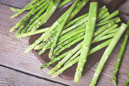 Asparagus bunch for cooked food, Bundle of fresh green asparagus on a rustic wooden table Imagens