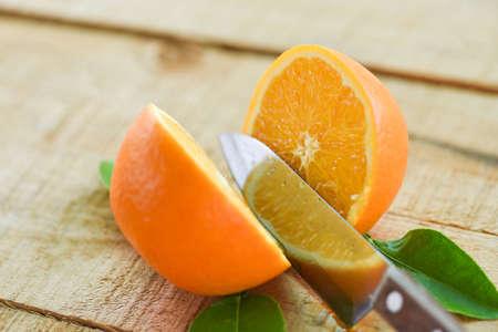 Fresh orange slice and leaves healthy fruits, Orange fruits with leaf kitchen knife on wooden background Imagens