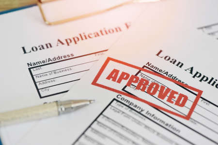 Loan approval, Loan application form with Rubber stamping that says Loan Approved, Financial loan money contract agreement company credit or person