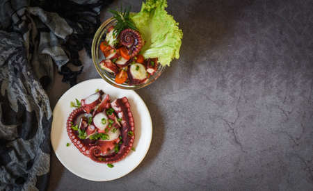 Fresh and healthy salad seafood squid and octopus tentacles, Octopus salad vegetables with lemon lime tomatoes chili herbs and spice on plate and bowl - top view