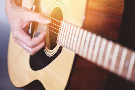 Home hobbies concept, Man hands playing acoustic guitar, close up guitar player Musical instrument for recreation or hobby passion Imagens