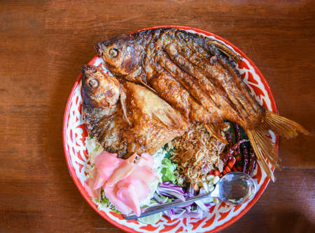 Fried fish with vegetable herb spices Thai food , pickled fish