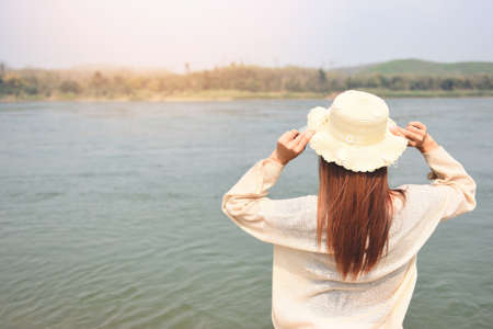 Woman on the beach concept, Young pretty woman in hat tropical beach sea island in the background. Beautiful vacation summer holiday fashion, girl on the river 写真素材 - 165333457