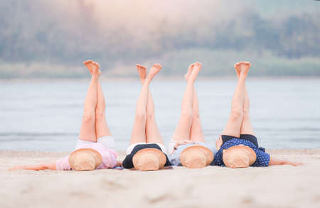 Woman on the beach relaxing concept, four women lying on sand tropical beach stretching up slender legs sea island in the background. Beautiful vacation summer holiday fashion
