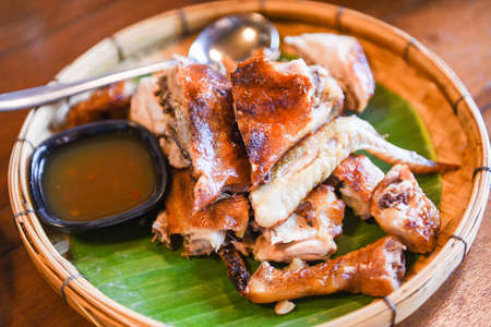 Grilled chicken Thai food with chili sauce on banana leaf and wooden background - Thai traditional menu