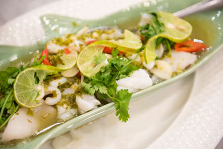 Steamed Squid with Lemon, hot and spicy squid steamed with lime - Thai food