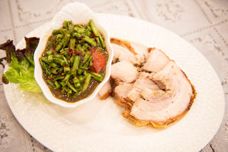 Spicy salad long bean and crispy pork sliced on white plate and vegetable Thai food , Crispy Pork Bean Salad