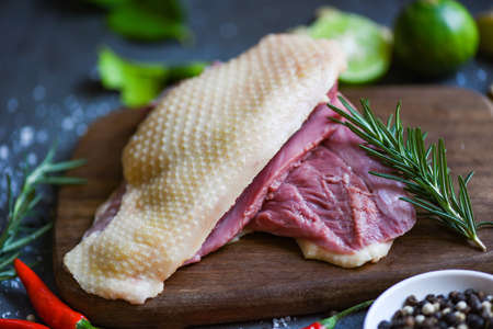 Fresh duck meat for food, Raw duck breast with herb spices ready to cook on wooden cutting board