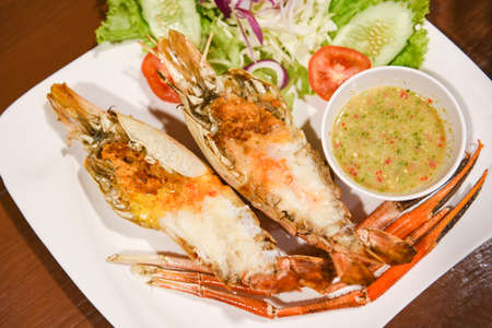 Grilled shrimp cut half with fresh vegetable and seafood sauce, Giant river prawn shrimp grilled serve on white plate 写真素材 - 165808561