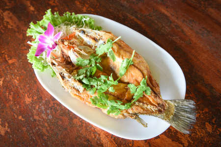 Fried fish with herb and vegetable, cooked food sea bass fish fillet on plate on wooden table