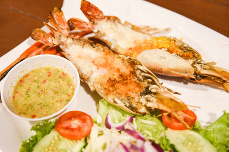 Grilled shrimp cut half with fresh vegetable and seafood sauce, Giant river prawn shrimp grilled serve on white plate
