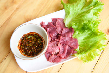 beef meat salad, fresh raw beef slice on plate with spicy sauce and vegetables lettuce - thai food Reklamní fotografie