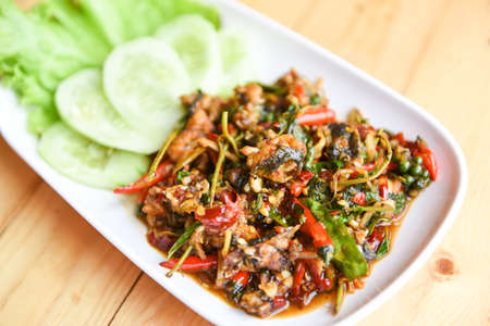 frog meat chopped puff hot and spicy with herb spices on plate food - Stir fried frog and chilli red curry
