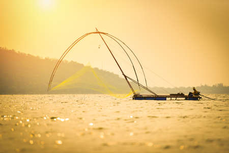 Asia fisherman net using on wooden boat casting net sunset or sunrise in the river - Silhouette fisherman boat with mountain island background on the sea ocean Reklamní fotografie