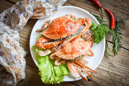 Fresh seafood crab on white plate cooking food in the restaurant, Steamed or boiled Blue Swimming Crab ocean gourmet with chili herb and spices lemon and rosemary on wooden dining table, top view