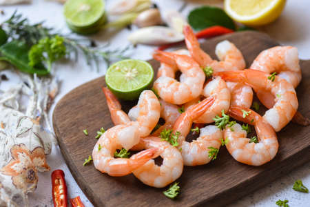 fresh shrimps served on wooden cutting board in the seafood restaurant, boiled shrimp prawns cooked with herbs and spice