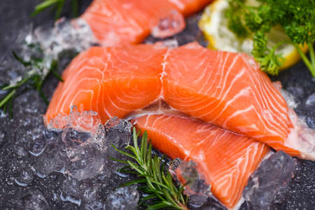 Raw salmon filet with herbs and spices on dark black background, Fresh salmon fish on ice