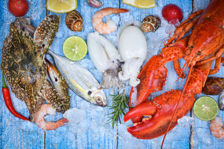 Fresh fish and seafood plate with Shellfish shrimps prawns crab shell squid octopus crab lobster and fish ocean gourmet dinner, Fresh raw seafood on ice with herbs and spices at the fish market food 版權商用圖片