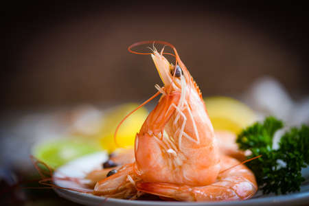 fresh shrimps served on plate in the seafood restaurant dark background, boiled shrimp prawns cooked with herbs and spice