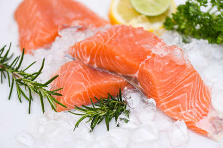 Raw salmon filet with herbs and spices on white background, Fresh salmon fish on ice
