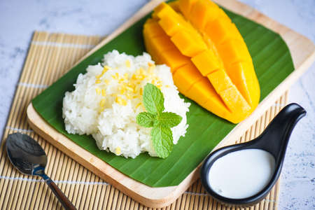 Ripe mango rice cooked with coconut milk, Sticky rice summer tropical fruit food Asian Thai dessert sweet mango peel and sliced on banana leaf and fresh mint leaves