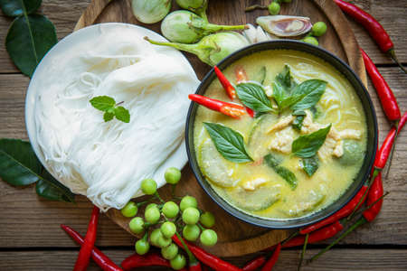Chicken green curry Thai food on soup bowl with rice noodles ingredient vegetable herbs and spices pepper chili wooden background, Traditional green curry chicken cuisine asian food. Top view 版權商用圖片