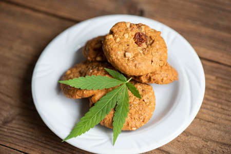 Chocolate cookies with cannabis leaf - marijuana leaves plant on white plate on the wooden table nature herb, cannabis food concept